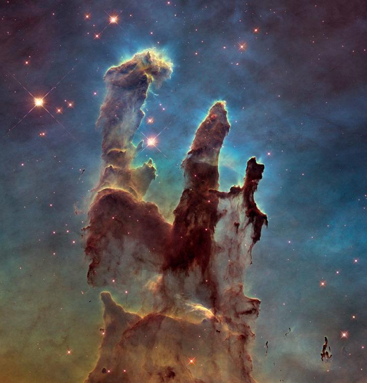 """Yksi tähtitieteen ikonisimmista kuva-aiheista ovat Kotkasumun """"Luomisen pilarit"""". Tämä kuva on otettu Hubble-avaruusteleskoopin 25-vuotisjuhlavuonna paremmalla kameralla, kun alkuperäinen Hubblen kuva vuodelta 1995 oli jo ennättänyt esiintyä elokuvissa, tv-sarjoissa, t-paidoissa, tyynyissä ja jopa postimerkissä. Pilarit osoittavat erehtymättä kohti noin neljää hyvin massiivista tähteä, jotka syntyivät sumussa ensimmäisten joukossa reilut miljoona vuotta sitten. Niistä massiivisin vastaa noin 80 Aurinkoa. Pilareista vasemmanpuolimmaisin on hiukan tähtiä kauempana siten, että sen meille päin näkyvä kylki näkyy selvästi valaistuna. Kaksi muuta pilaria on hiukan meitä lähempänä, ja ne näyttävät meille varjoiset selkäpuolensa. Myös Auringon uskotaan muodostuneen Kotkasumun tapaisessa ympäristössä. Aurinkokunnasta on löytynyt radioaktiivisia alkuaineita, joita uskotaan syntyvän vain massiivisten tähtien räjähtäessä supernovina. Aurinkokunnan kehittyessä lähistöllä on siis ollut vasta muodostunut, nopeasti kehittynyt massiivinen tähti – samanlainen kuin ne, jotka ovat säteilyllään muovanneet Luomisen pilarit. Kuva NASA, ESA / Hubble and the Hubble Heritage Team"""