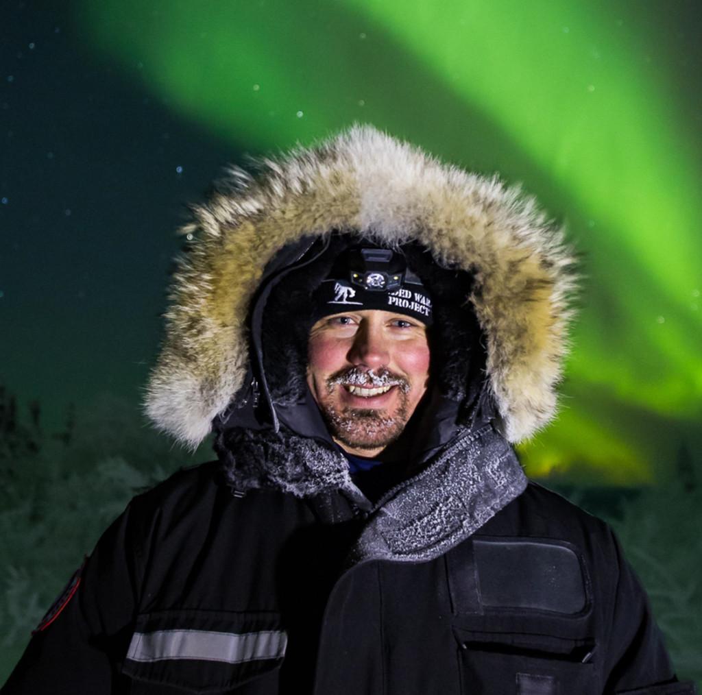 Kokenut revontulikuvaaja Ronnin Murray. Fokus on etualalla ja havaitsija valaistaan erillisellä valonlähteellä.
