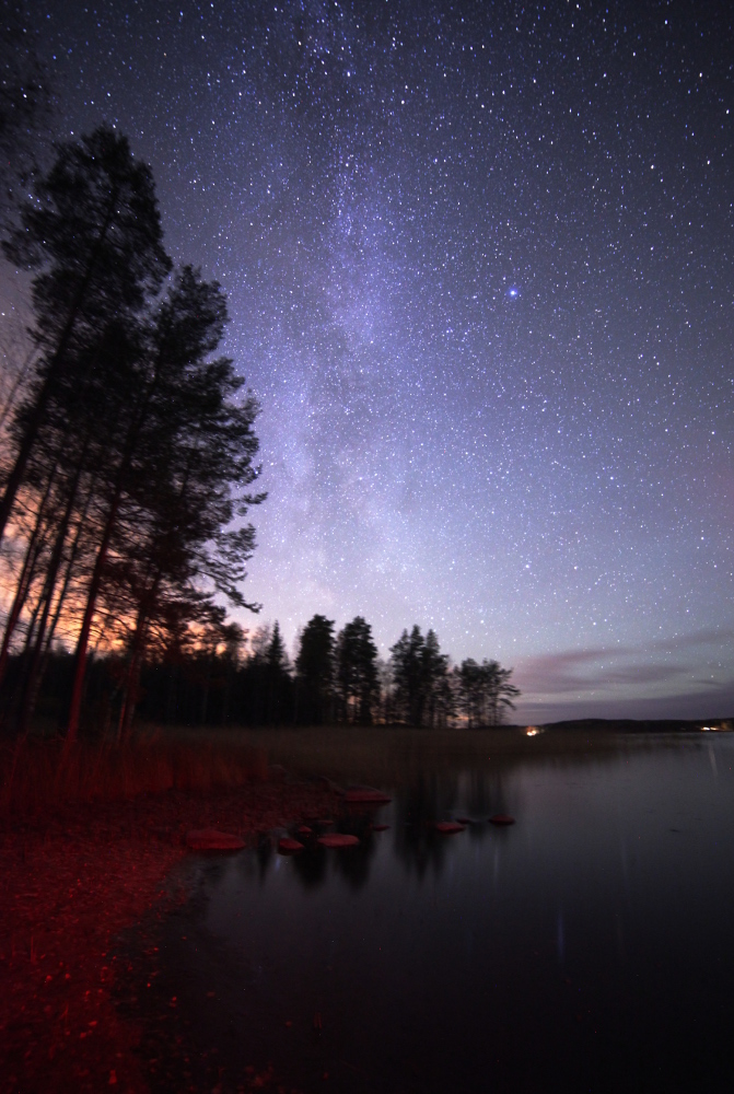 Kuvan etualaa on pyyhkäisty punaisella taskulampulla. Imatran pilvistä heijastuva hukkavalo on piilotettu puiden taa. Kuva Emma Bruus