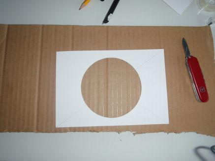 Kuva 2. Reiän leikkaaminen kartonkiin. Reiän halkaisija vastaa havaintovälineesi objektiivipään halkaisijaa.