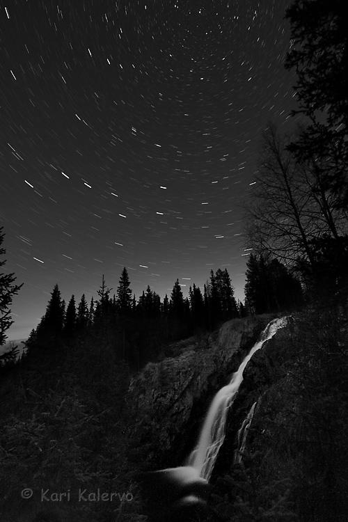 Ansel Adamsin jalanjäljillä Hepokönkäällä, metsän takaa kajastaa heikko revontulivalo. Mustavalkokuvauksen mestari Adams ei tainnut kuvata viirutähtiä, mutta tuli kuuluisaksi mm. vesiputouskuvistaan. Kuva: Kari Kalervo.