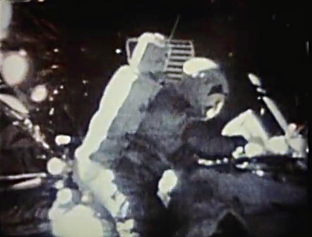 """David Scott leimaamassa postimerkkiä. Kuvakaappaus Nasan videolta """"Apollo 15: In the Mountains of the Moon"""" (HQ-217)."""